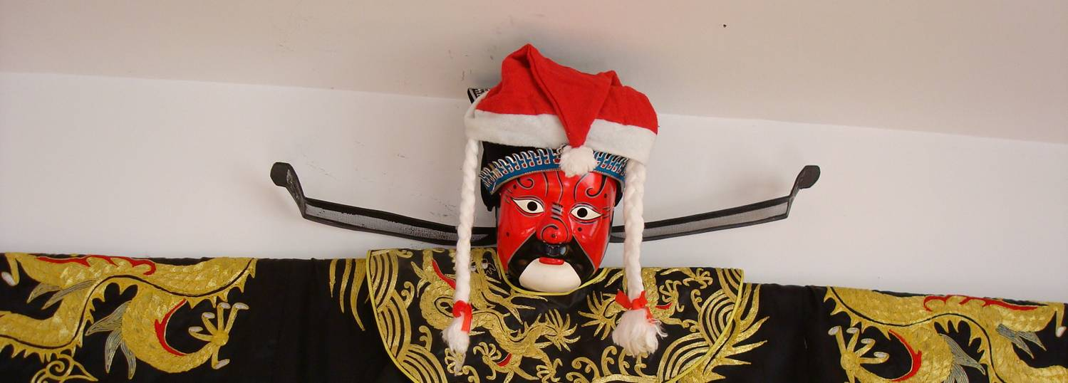 Picture: The emperor robe and mask wall hanging, wearing a Santa hat for the Christmas season.  Jiangnan University, Wuxi, China.