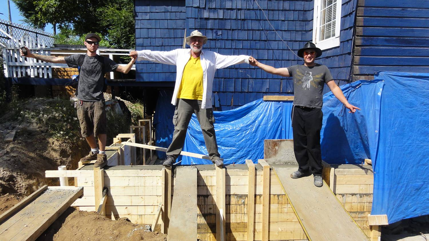 Picture:  D.J., David and Victor celebrate the completion of a section of hand mixed concrete wall.  Nanaimo, B.C.