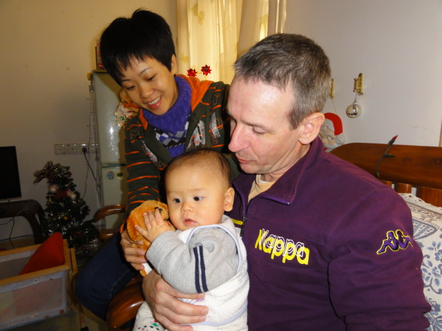 Pictre:  Xiao Hua, baby Padraig, and proud father Patrick.  Ruth Anderson photo.  Haikou on Hainan Island, China