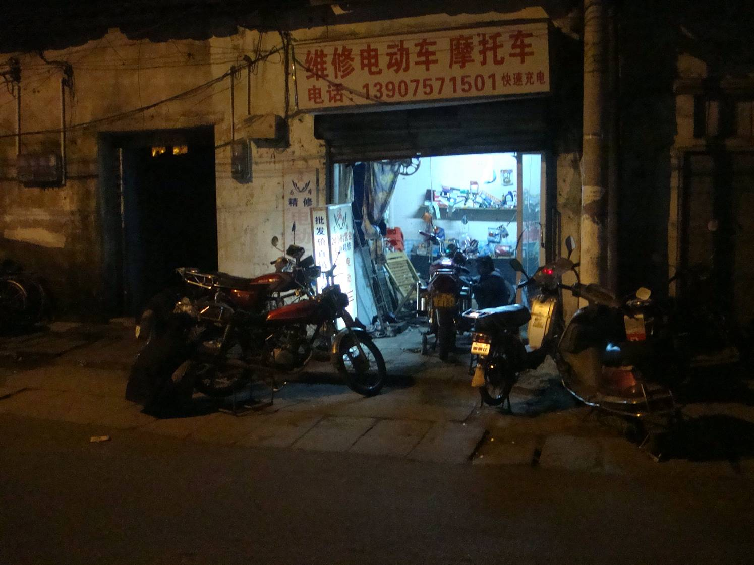 Picture:  Motorcycle maintenance goes late into the evening.  Haikou on Hainan Island, China