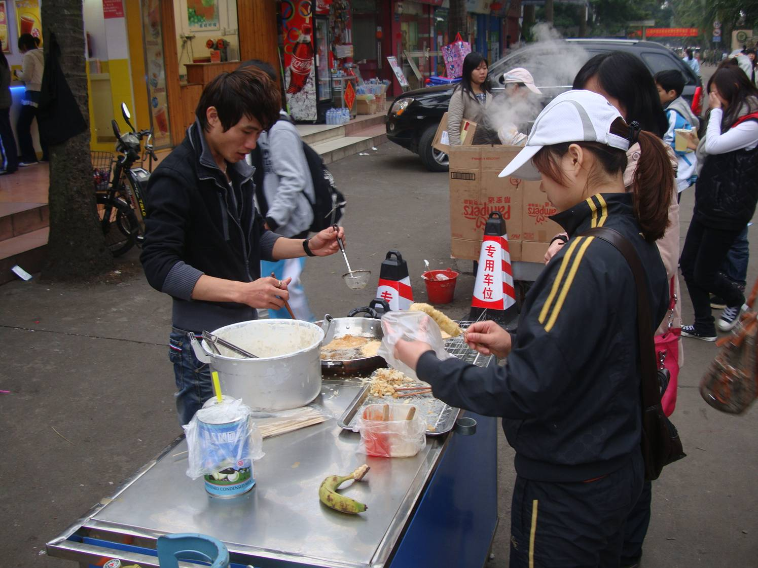 Picture:  This team of entrepreneurs have a deep frier set up on the street for plantain and bananas.  Tasty stuff.  Haikou on Hainan Island, China