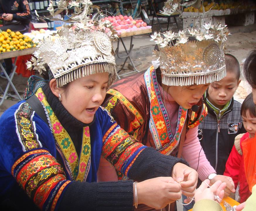 Picture:  Young ethnic minority girls sell their silver jewelry outside the gates of Hainan Normal University.  Haikou on Hainan Island, China