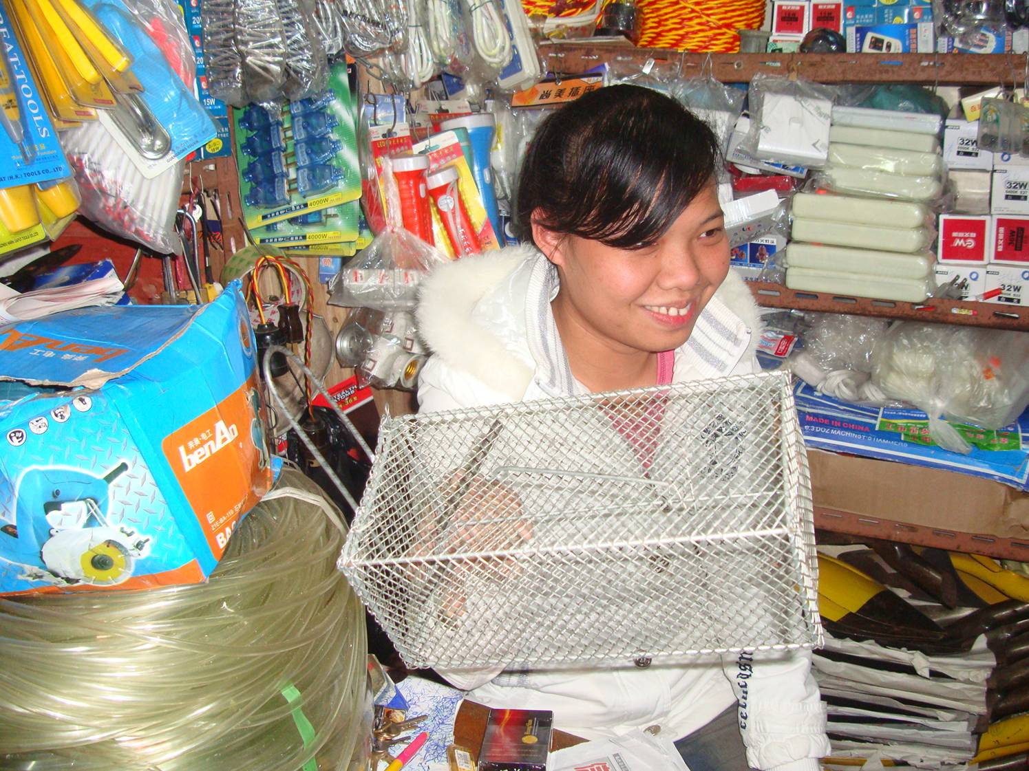 Picture:  The shop assistant holds a very effective live animal trap.  Haikou on Hainan Island, China
