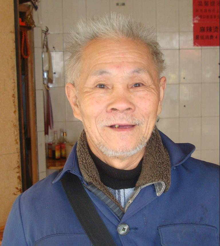 Picture:  The restaurant owner, and a fine set of tooth he has. He was kind enough to take his cigarette out to the street when I asked him to. Haikou, Hainan Island, China