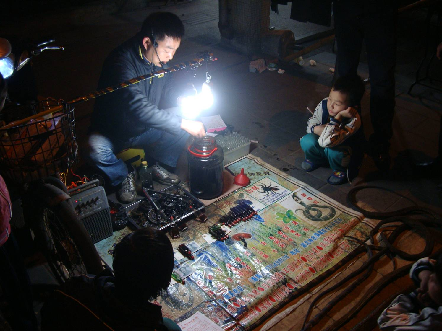 Picture:  That last of a dying breed, a real live snake oil salesman on the night streets of Haikou, Hainan Island, China.