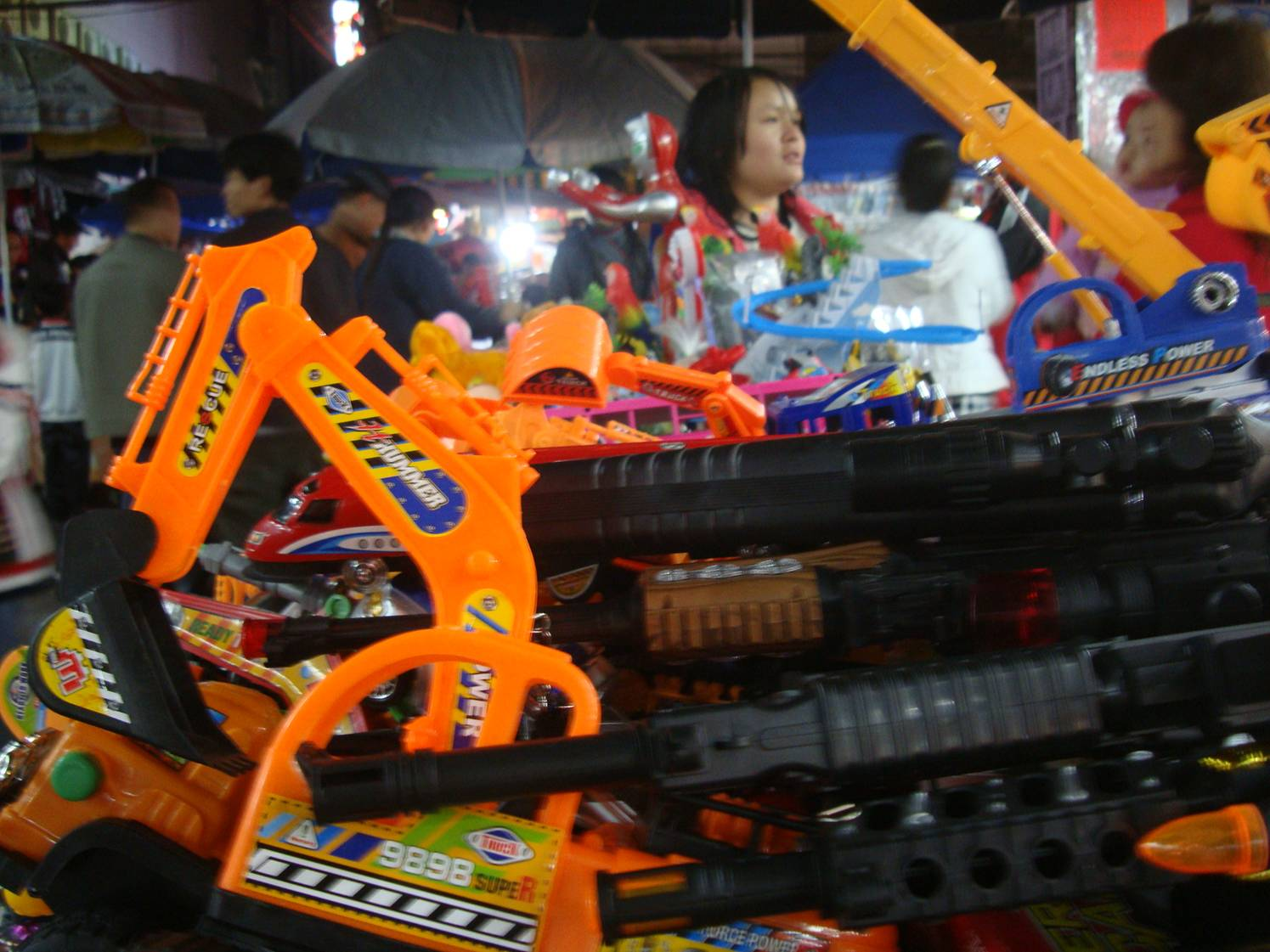 Picture:  A toy store in the center of the crowded street where the night market  blooms each evening.  Haikou on Hainan Island, China