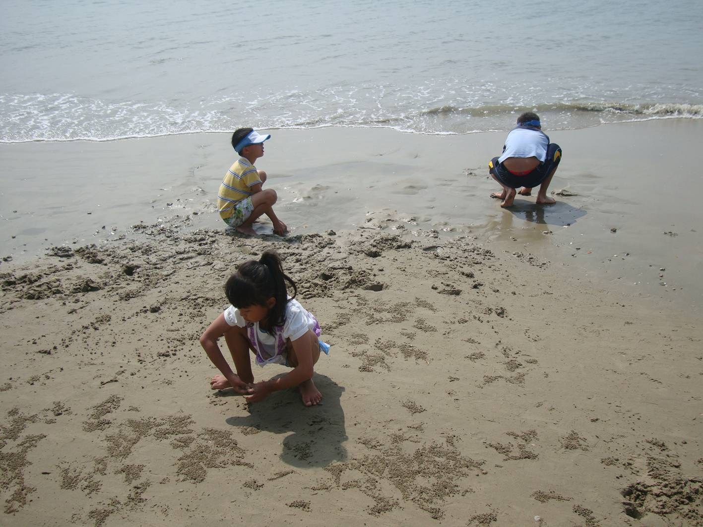 Picture:  Kids chase tiny crabs on the beach of Sanya, Hainan Island, China