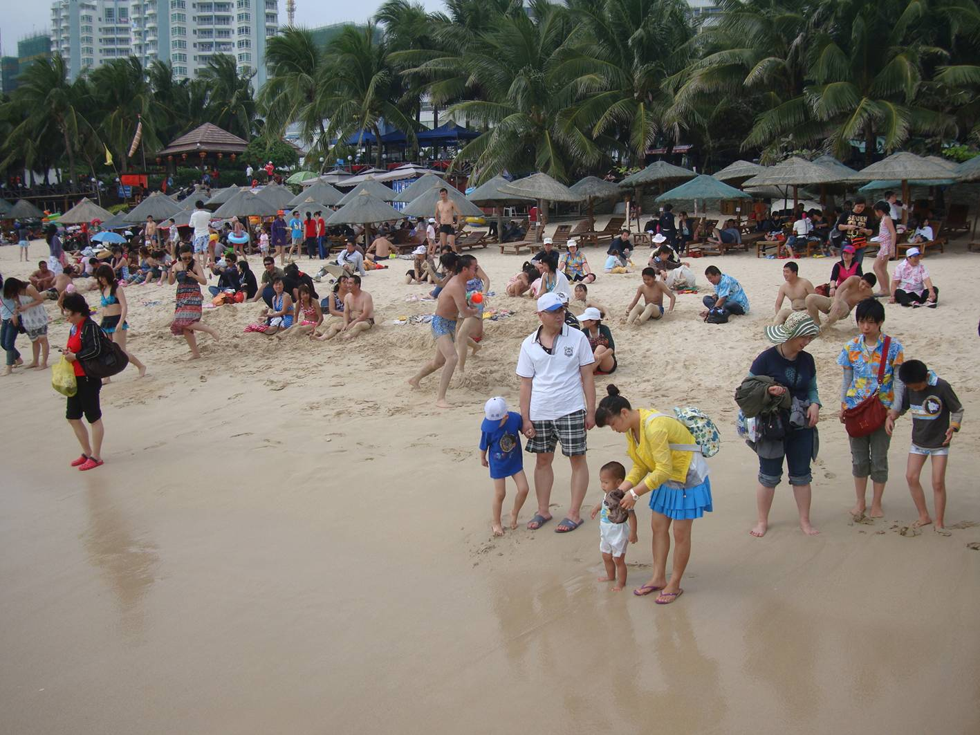 Picture:  Some of the visitors enjoyed being buried in the sand.  The beach at Da Dong Hai,  Hainan Island, China