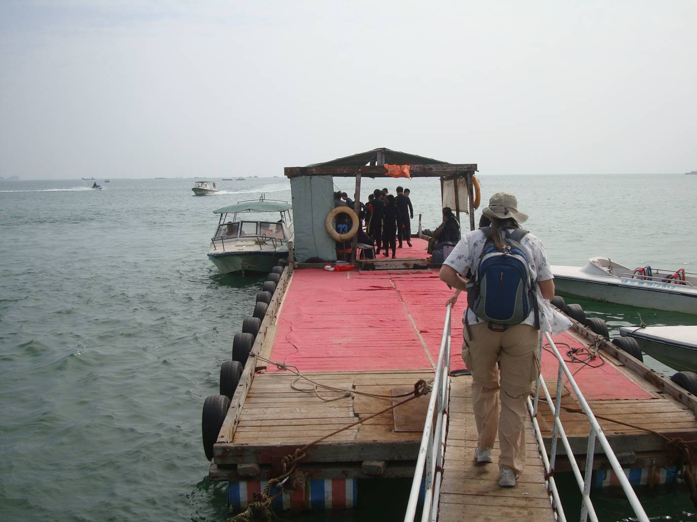 Picture:  Ruth walks the plank to the boat that will take us on the submarine ride adventure.  Da Dong Hai, Sanya, Hainan Island, China