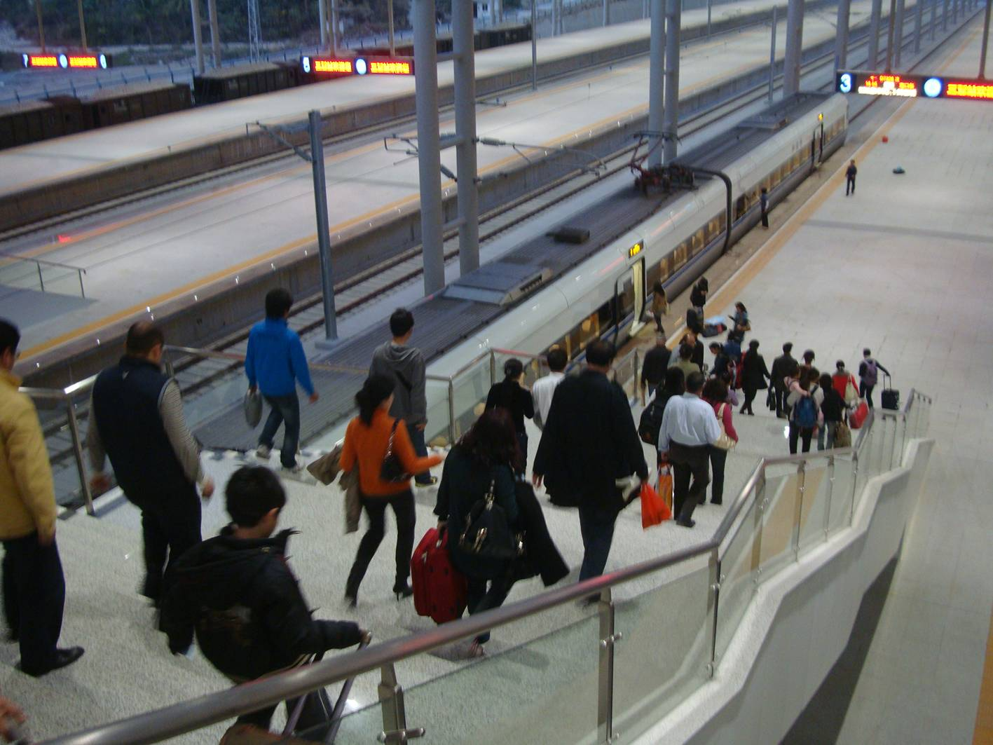 Picture:  Passengers stream down the stairs to the new fast train in the Sanya station.  Sanya, Hainan Island, China