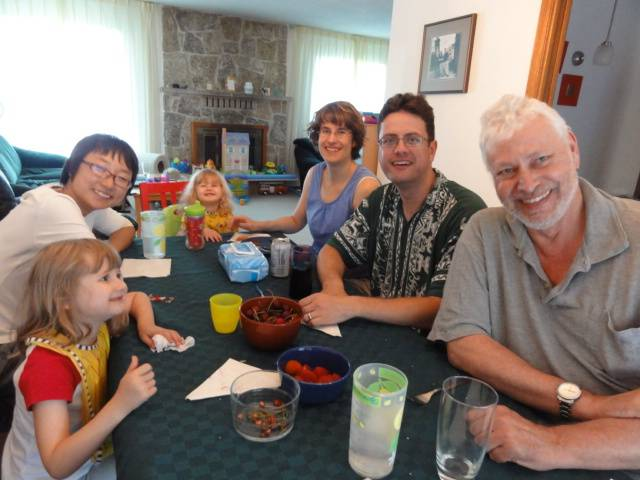 Picture:  A traditional Canadian dinner - bbq hamburgers- with a traditional Canadian family.