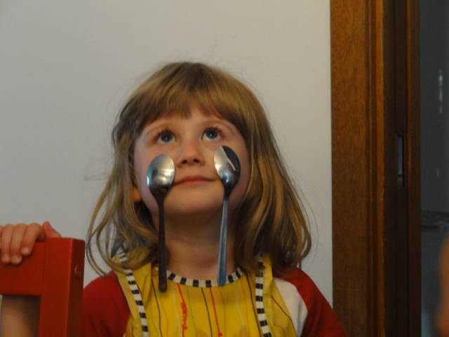 Picture:  The eldest daughter hangs two spoons on her face.  No glue.  No hands.