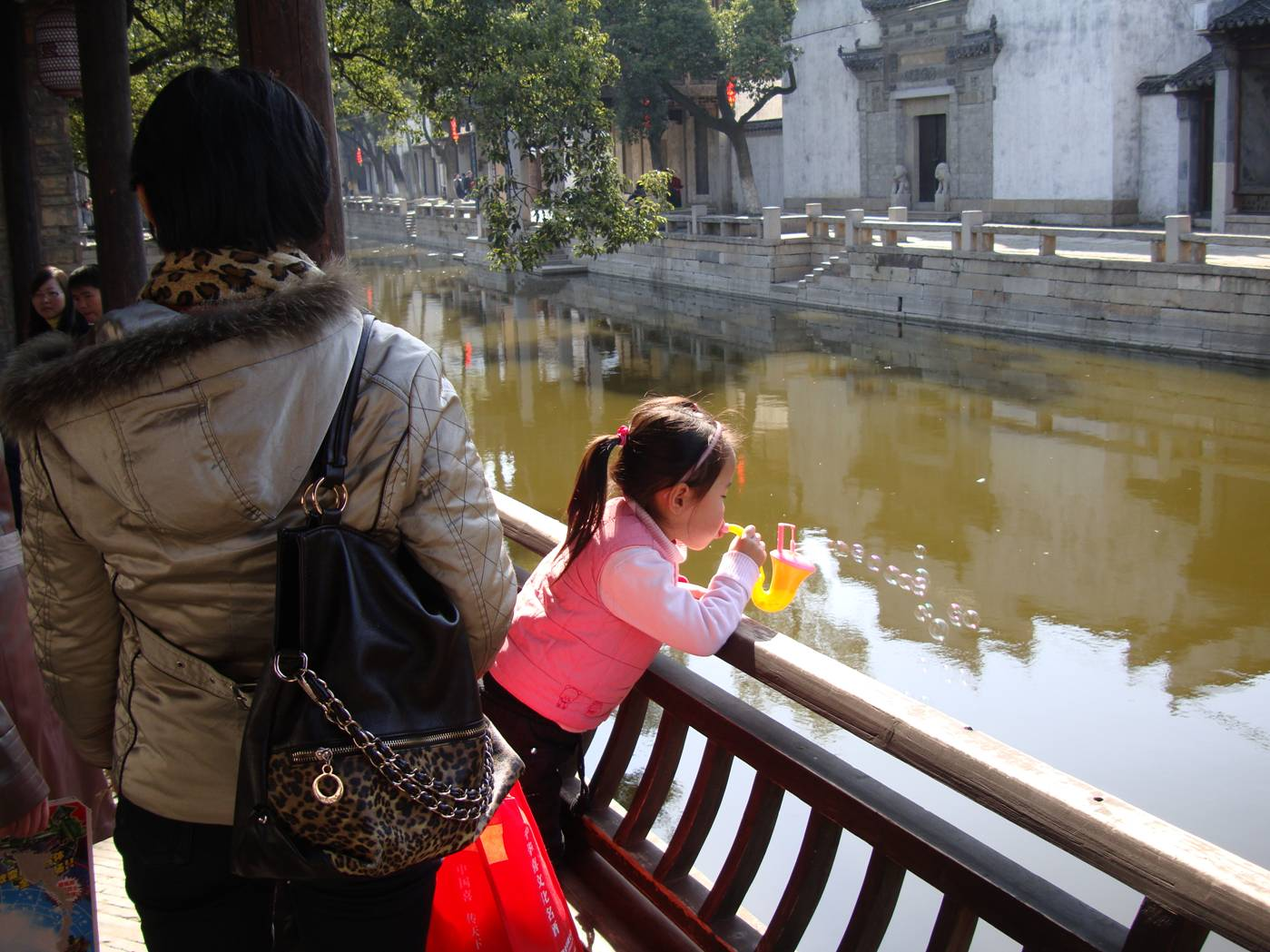 Picture:  A child blows bubbles over the canal.  Wuxi, China
