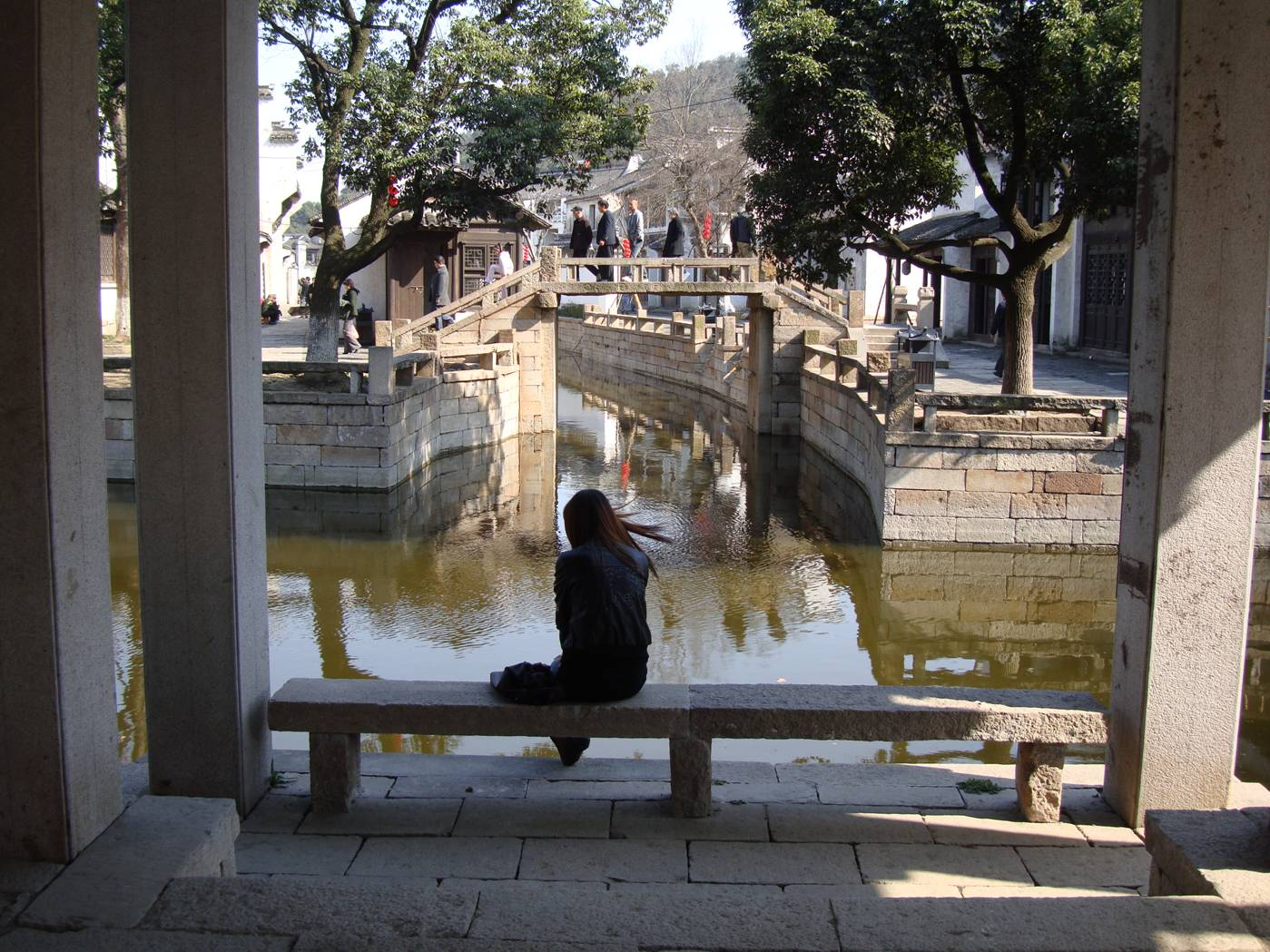 Picture:  A girl waits beside the sunlit canal.  Wuxi old city, Wuxi, China