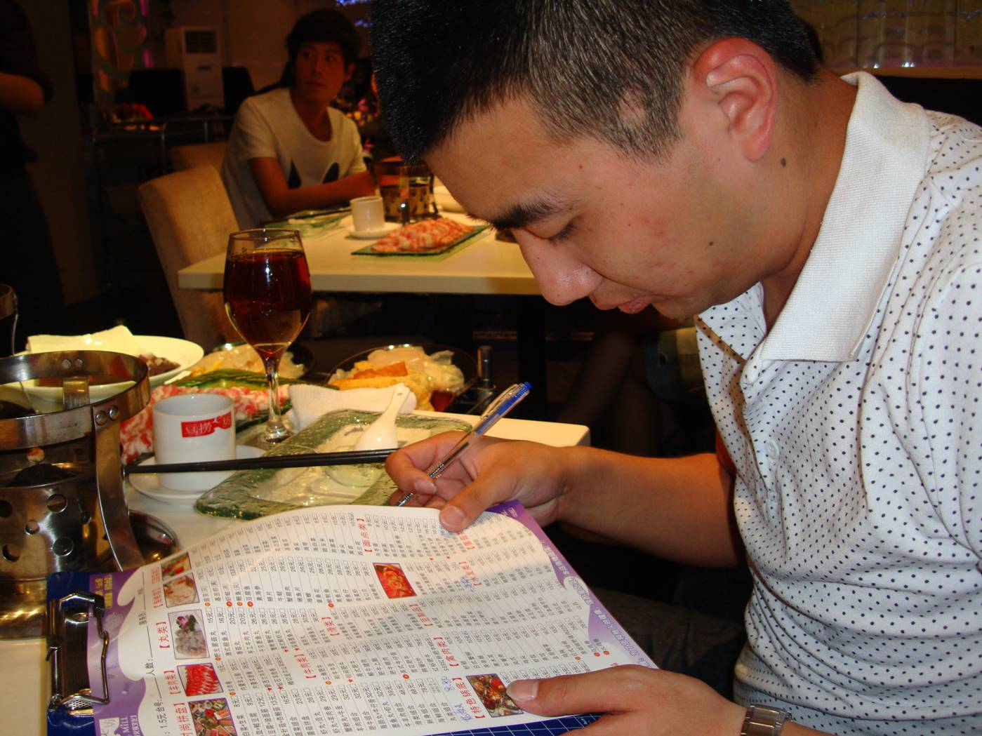Picture:  Clark scans the menu before ordering for all of us.  Hotpot dinner in Wuxi, China