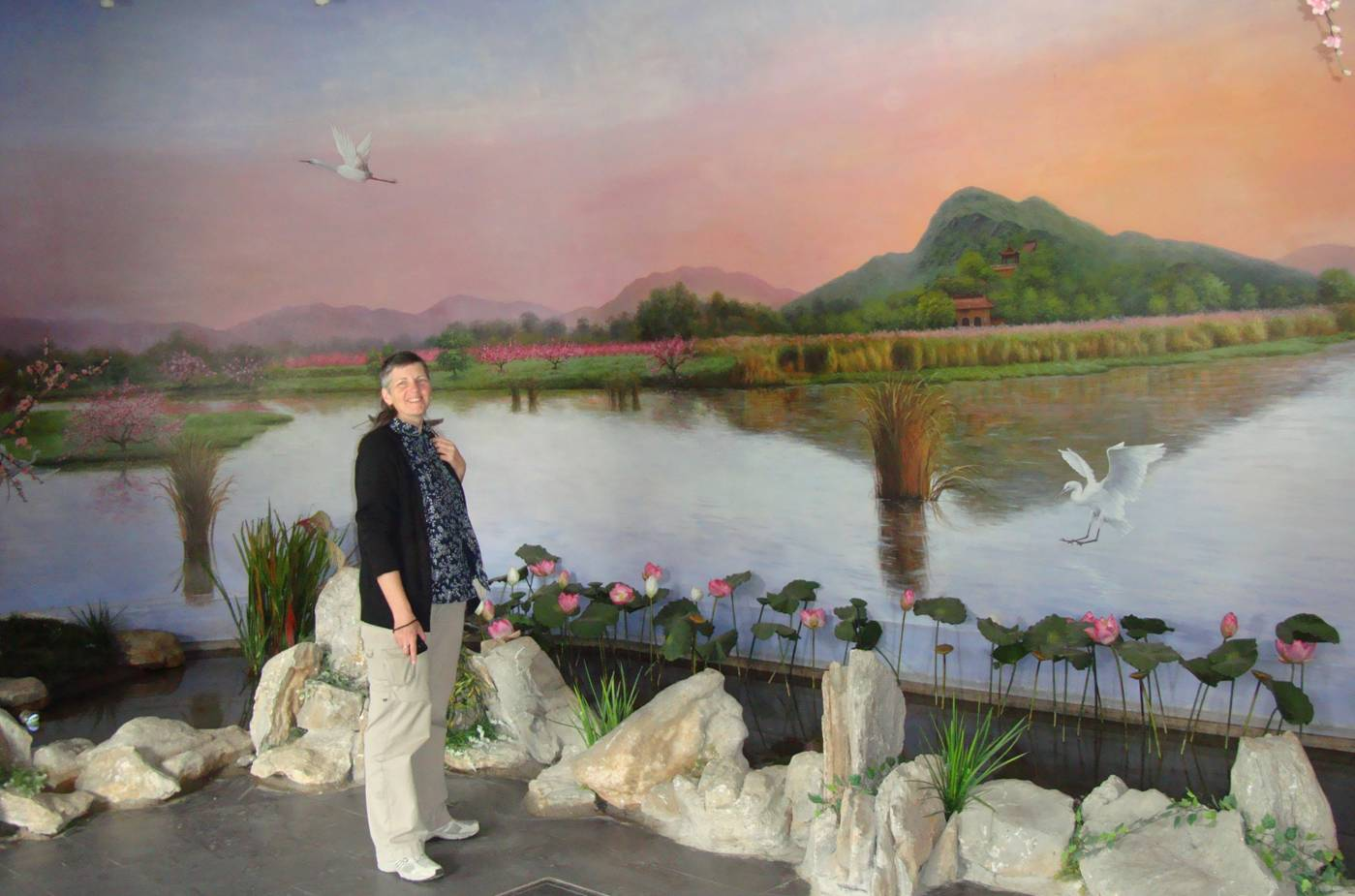 Picture:  Ruth stands in front of a huge mural depicting the orchards of Yang Shan.  The Tao Bo Yuan (Peach Museum), Yang Shan, Wuxi, China