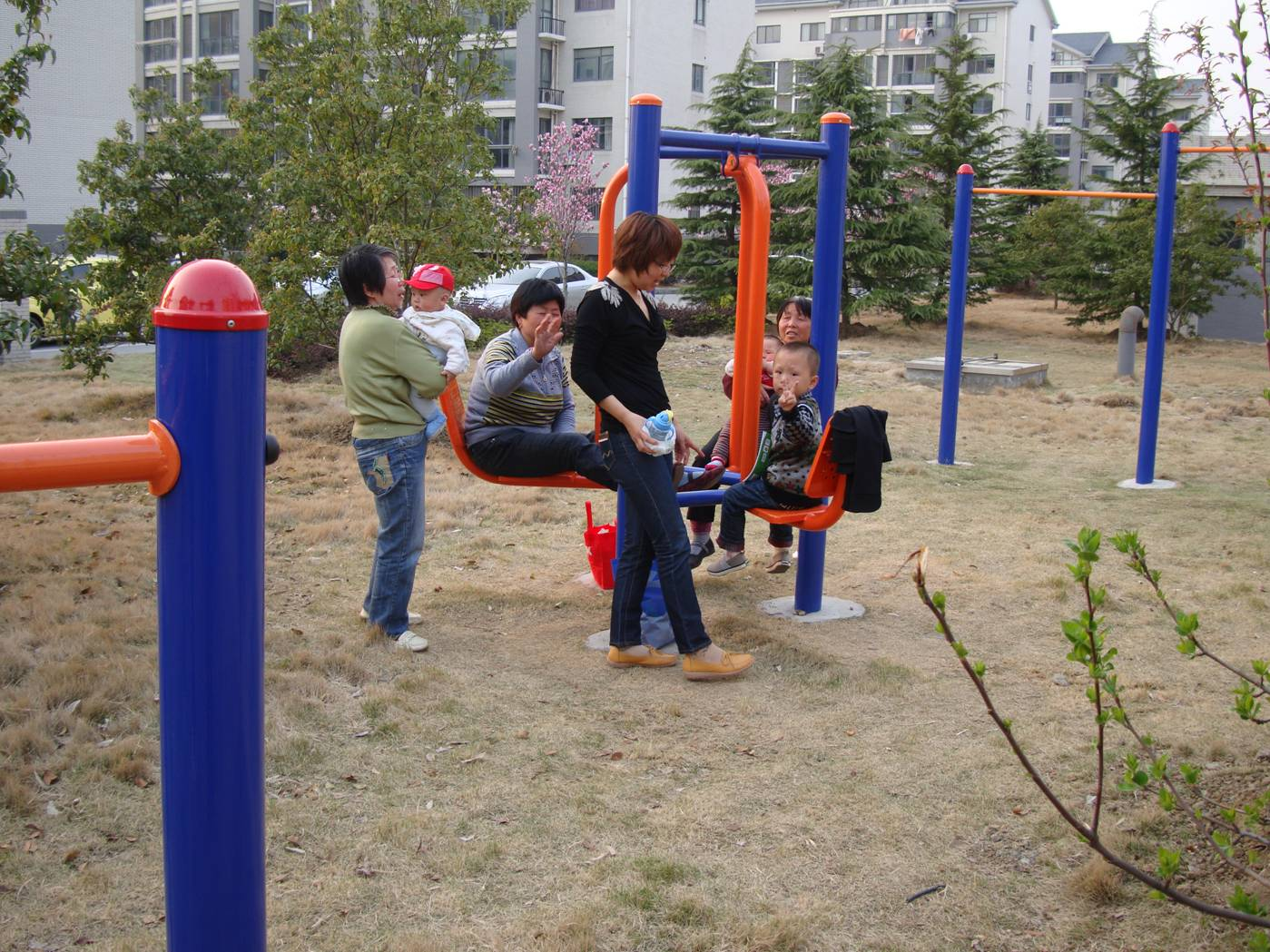 Picture:  Grandmothers and moms and kids enjoy the equipment in the new playground behind our apartment.  Jiangnan University, Wuxi, China