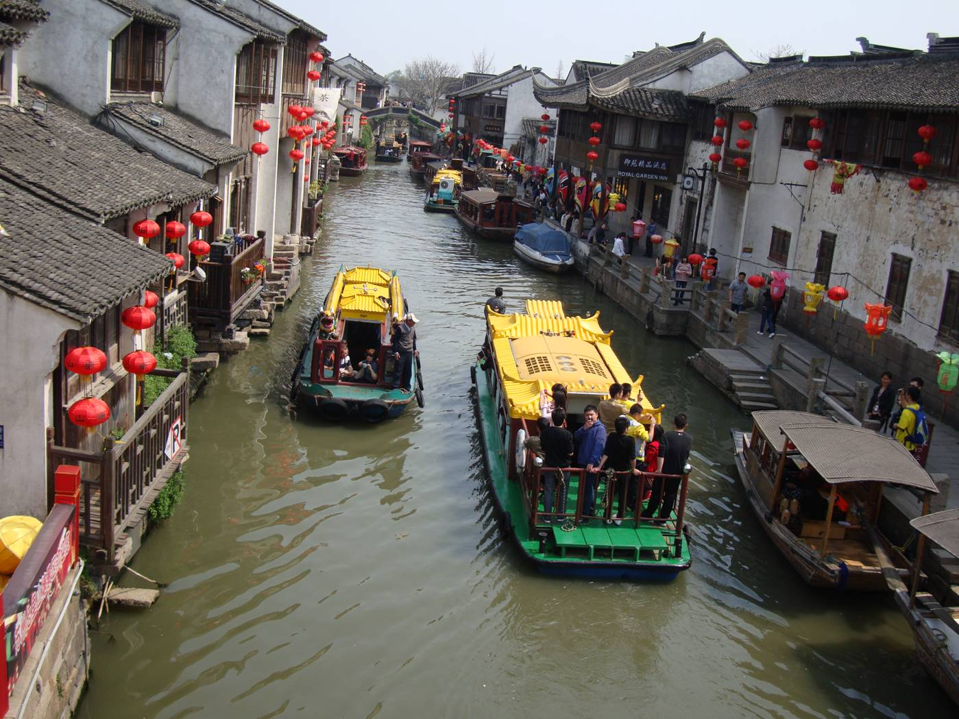Picture:  Tour boats on the Suzhou canal as seen from a bridge.  It's a colourful city this time of year.  Suzhou, China