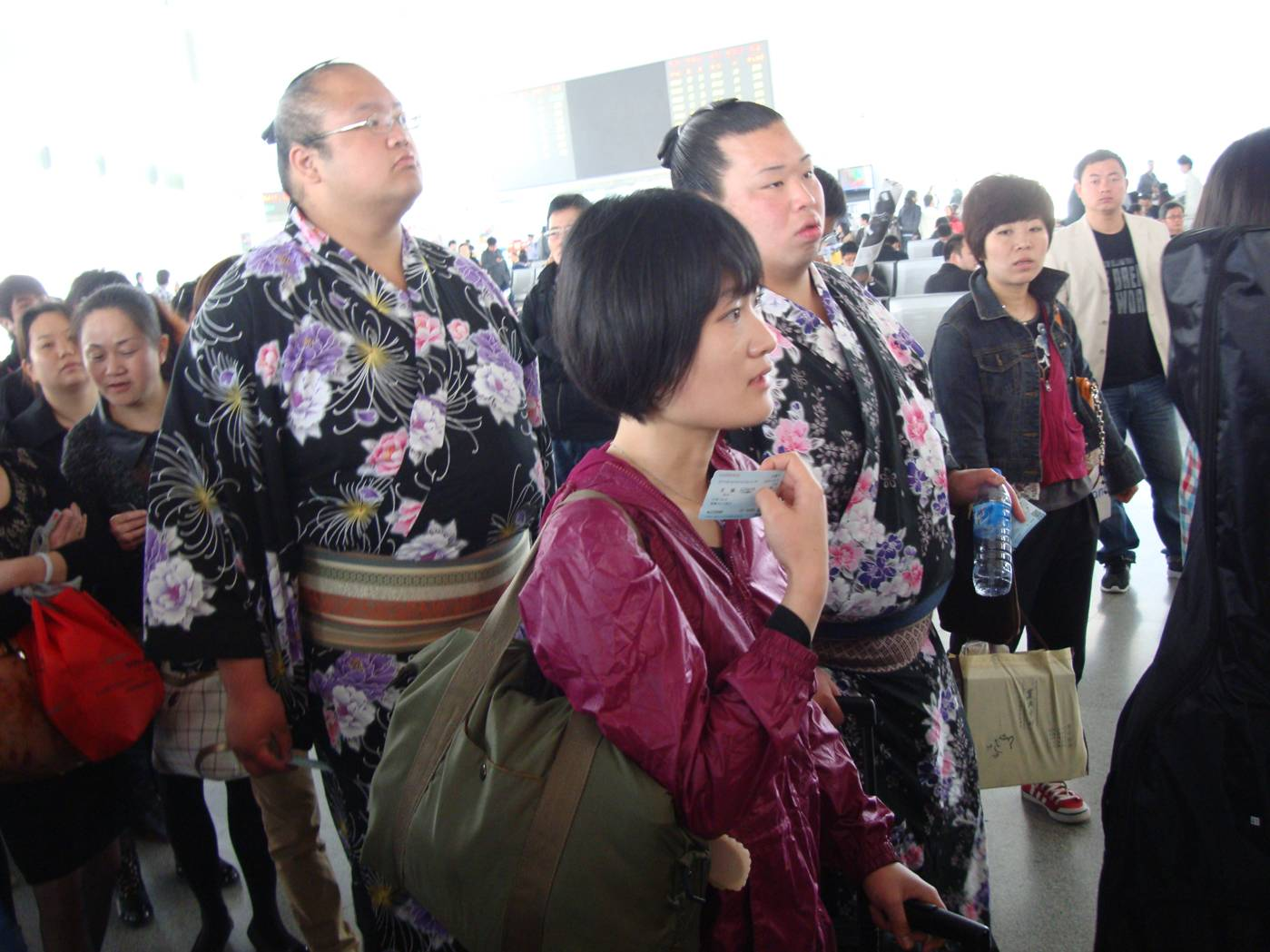 Picture:  Two Japanese sumo wrestlers in the lineup for the train in Wuxi train station.  Wuxi, China