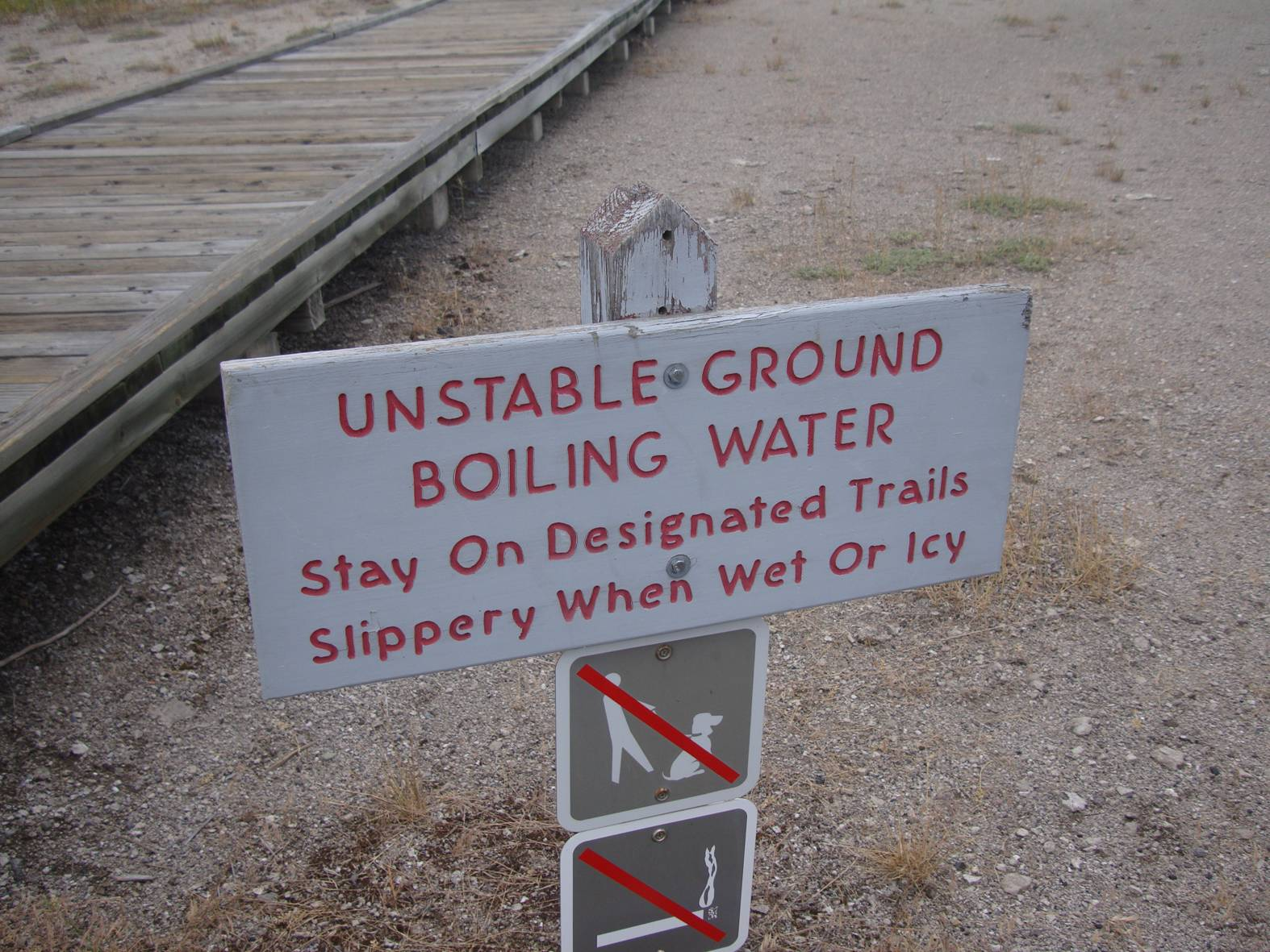 picture:  warning sign saying that one risks death by wandering from the path.  Yellowstone Park