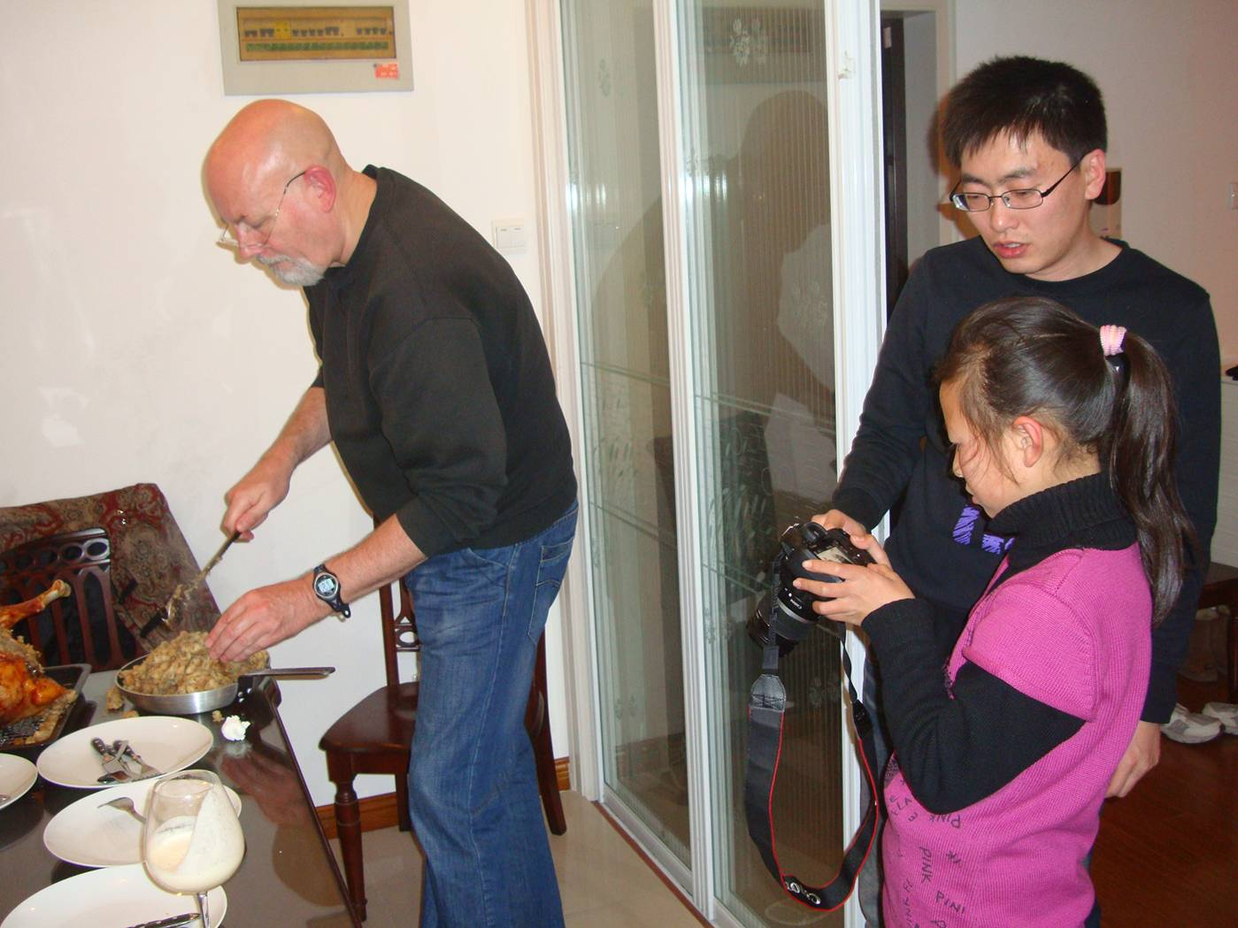 Picture:  Every event needs documentation.  Rob ladles out the stuffing while a very serious seven year old refines her camera technique. Christmas in Nantong, China