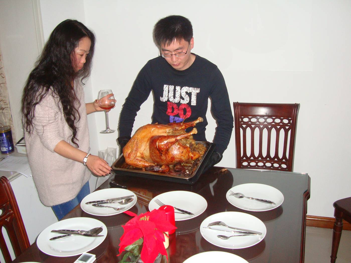 Picture:  Michelle supervises as Simon, our former student from Weihai, sets the turkey on the table.  Christmas in Nantong, China