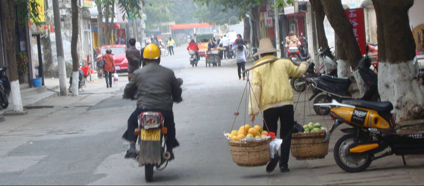 Picture:  A woman carries a heavy load of fruit to the market in Haikou, Hainan Island, China