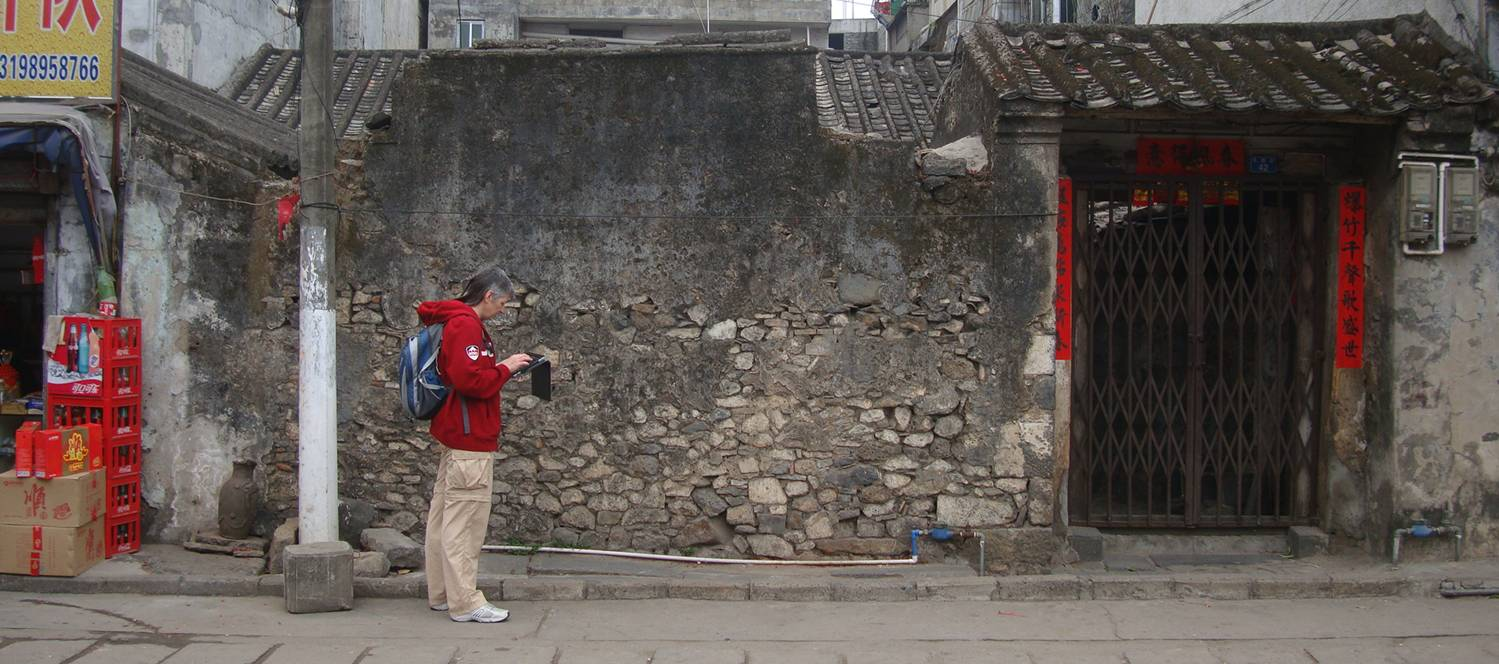 Picture: Old and new - Ruth checks her Google map on her iPad in front of a beautifully textured ancient wall in Haikou, Hainan Island, China