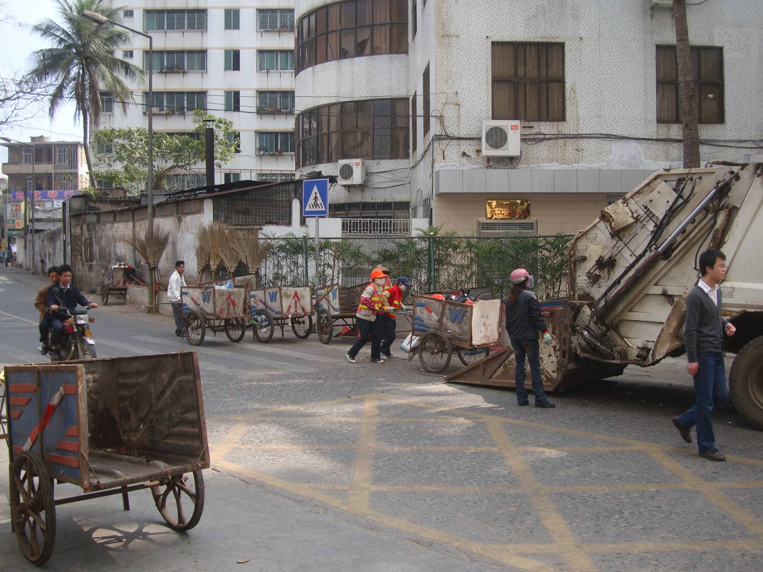 Picture:  Street sweepers gather with their carts to deliver the nights work to a garbage truck.  Haikou, Hainan Island, China