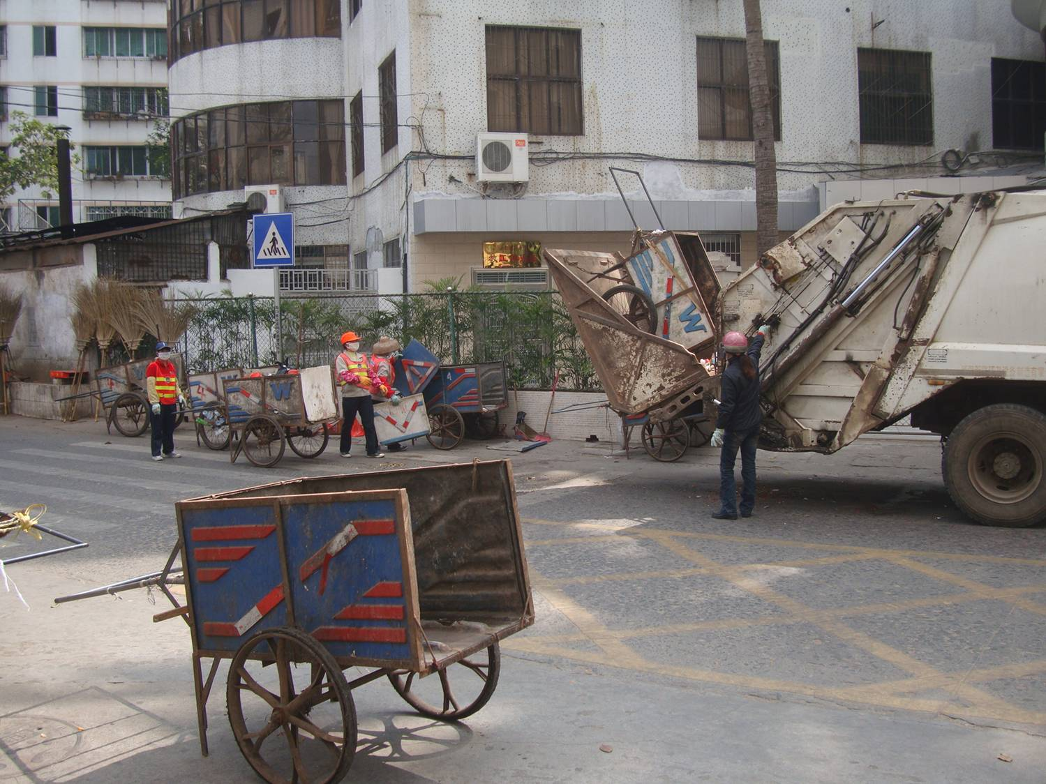 Picture:  A garbage truck empties a street sweeper's cart.  Haikou, Hainan Island, China