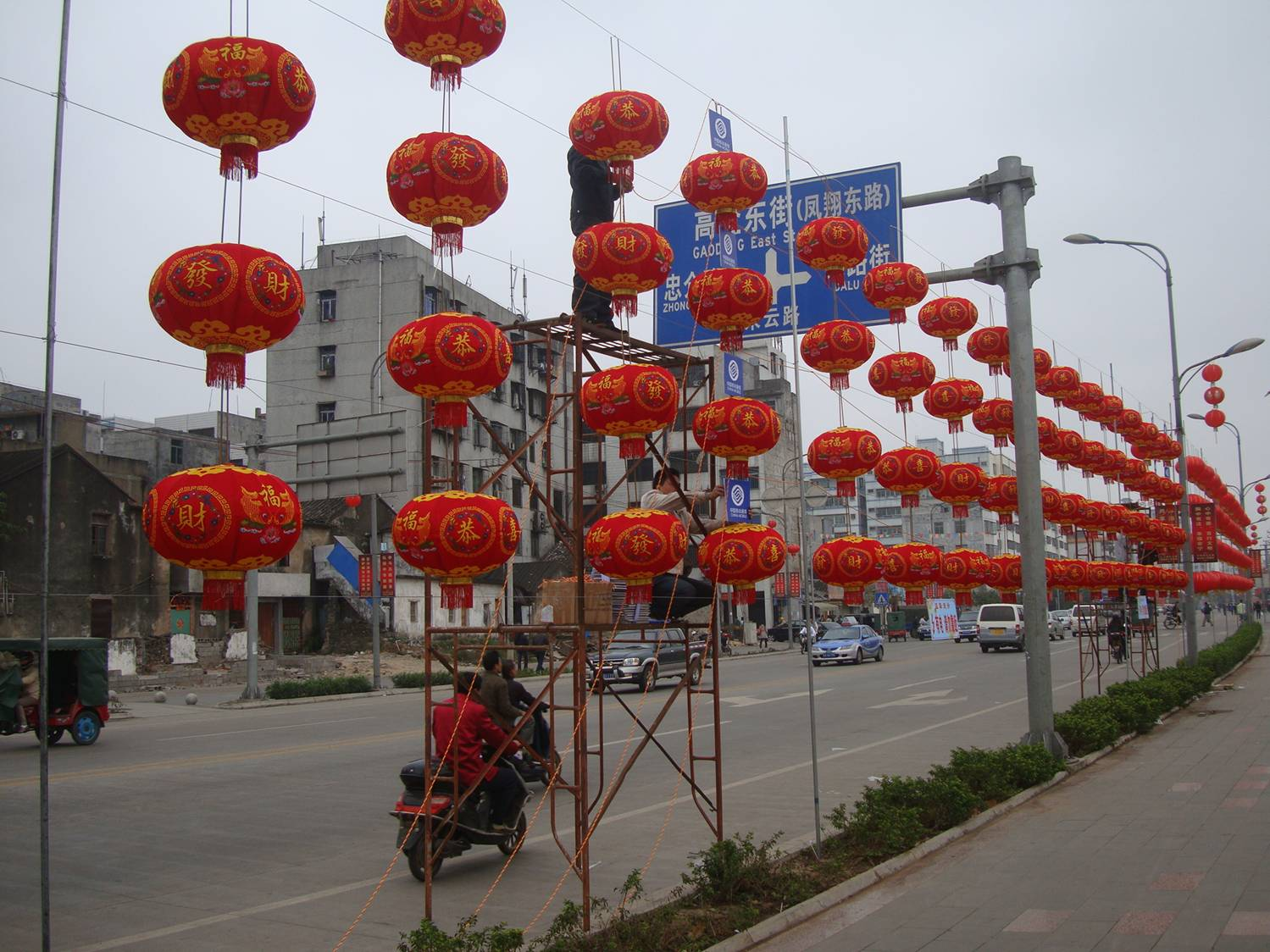 Picture:  Four rows of closely spaced red lanterns for the Lantern Festival stretch into the distance along a street in Haikou, Hainan Island, China