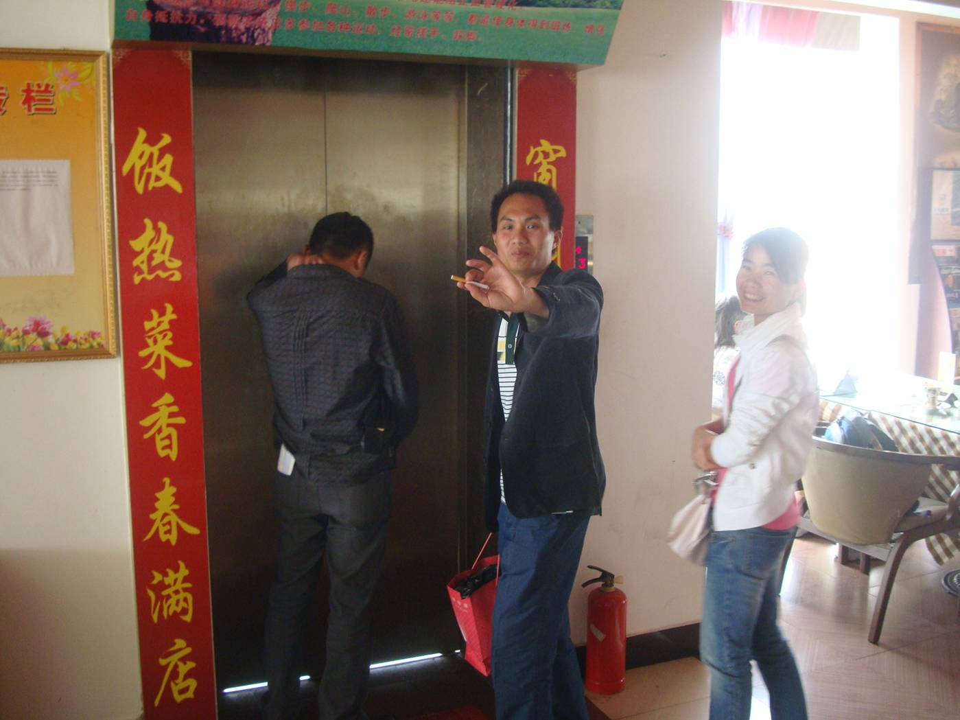 Picture:  He was about to walk into that elevator with that cigarette and not a moment's thought.  Haikou, Hainan Island, China