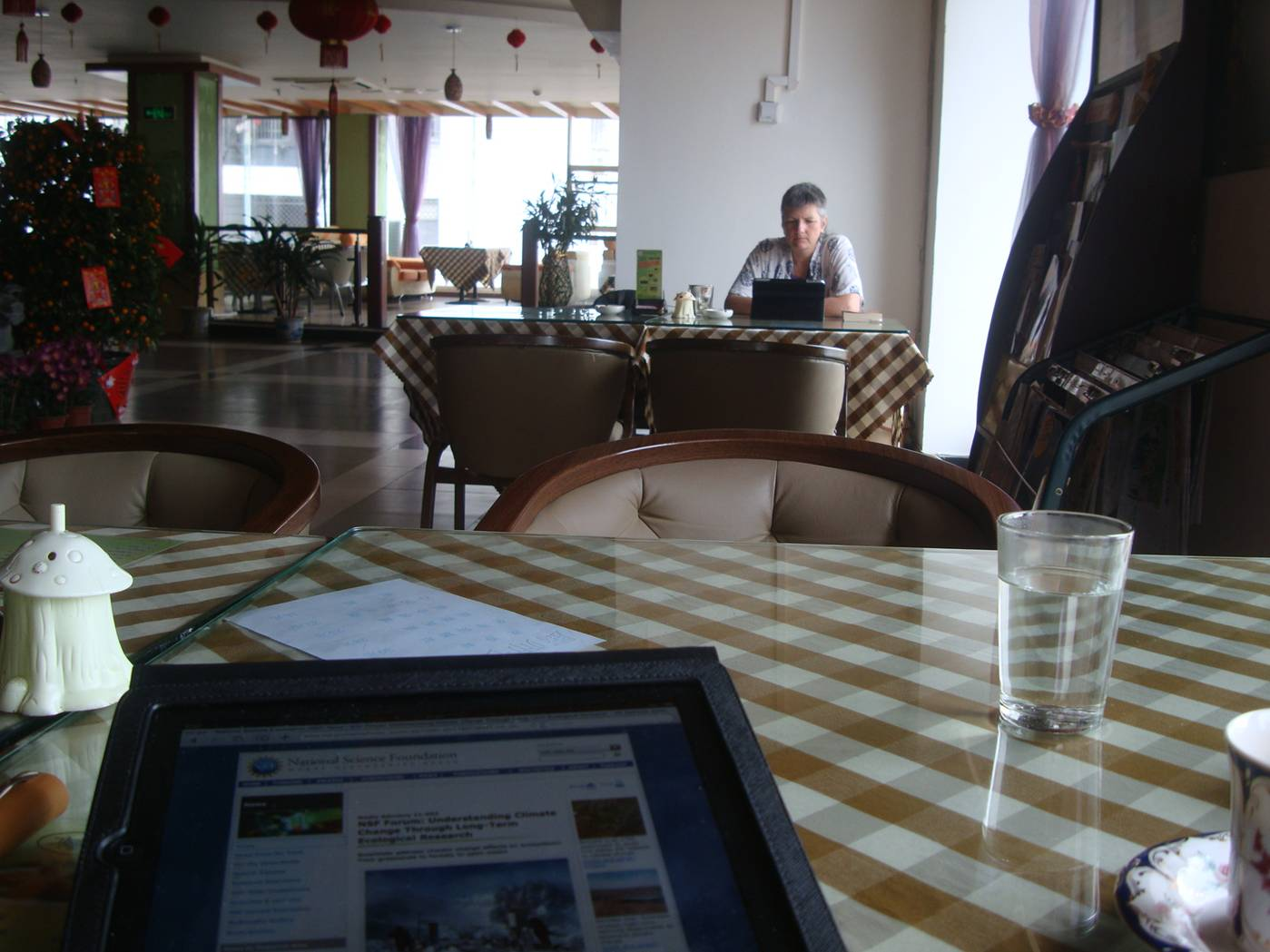 Picture:  My iPad on the foreground table, while Ruth works on the distant one in our own self-created no smoking section.  Haikou, Hainan Island, China