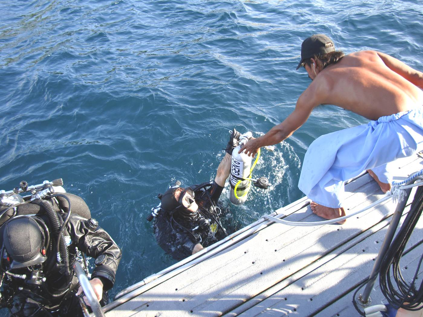Picture:  Doug helped out of the water after his dive.  Phuket Island, Thailand.
