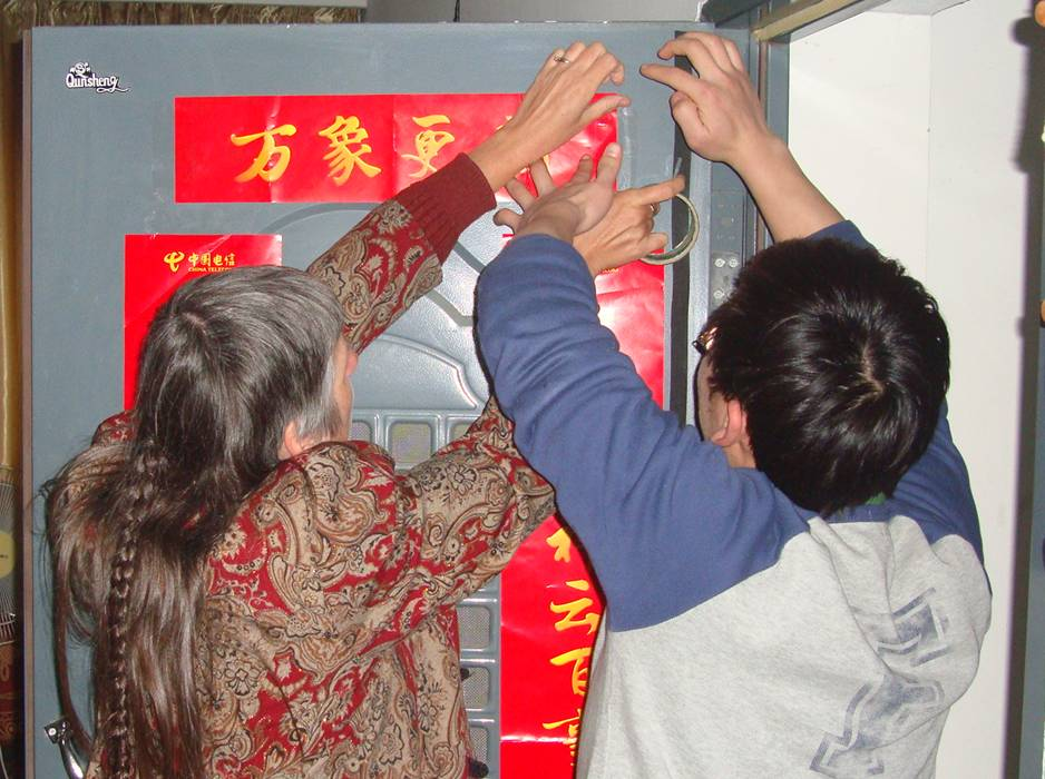 Ruth and Wang Yijing decorate our door in the traditional fashion.  Jiangnan University, Wuxi, China