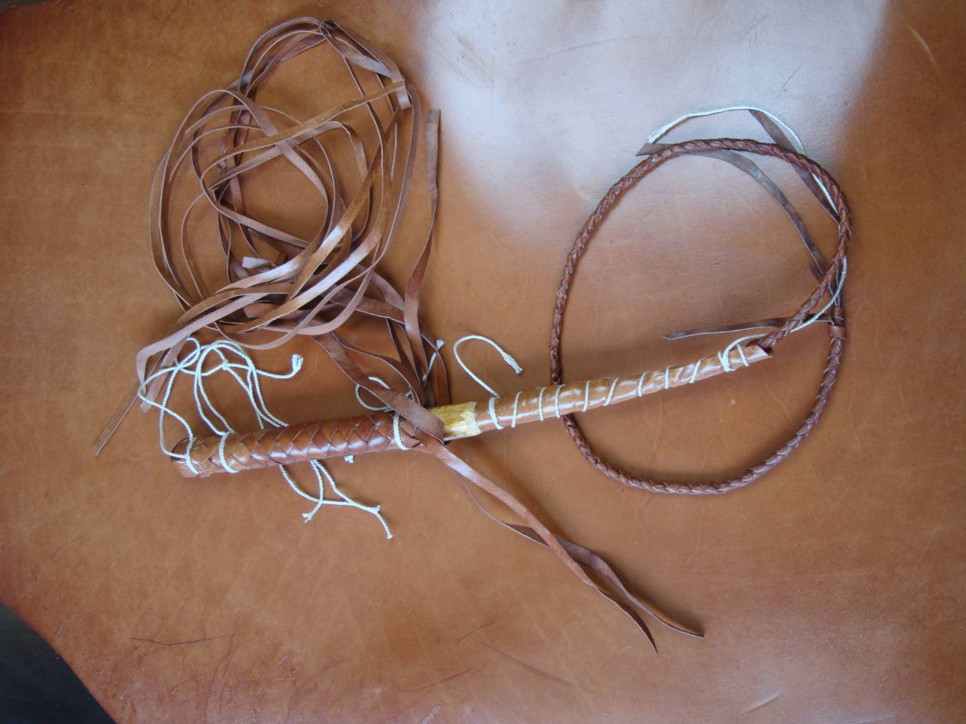 Picture:  The beginnings of my second bullwhip. It has a steel core inside a bamboo cover, with four ply braiding over the head to make sure it all stays together.  No less work than the first one.