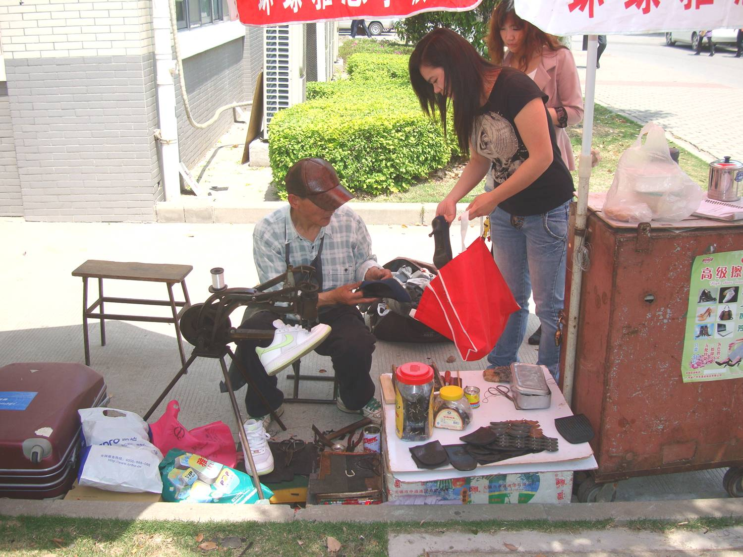 Picture:  A shoe repairman can set up his shop anywhere, and seems to be doing a lot of business.  Jiangnan University, Wuxi, China