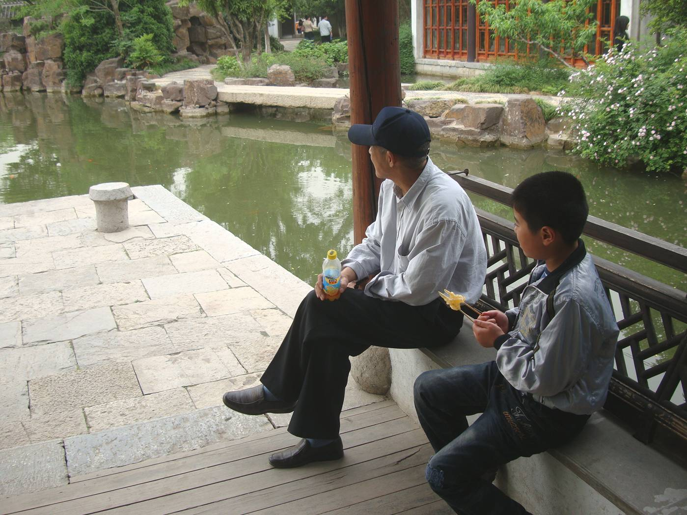 Picture:  A father and son take a minute to enjoy the serenity of the pond.  The museum grounds near Xi Hui Park, Wuxi, China