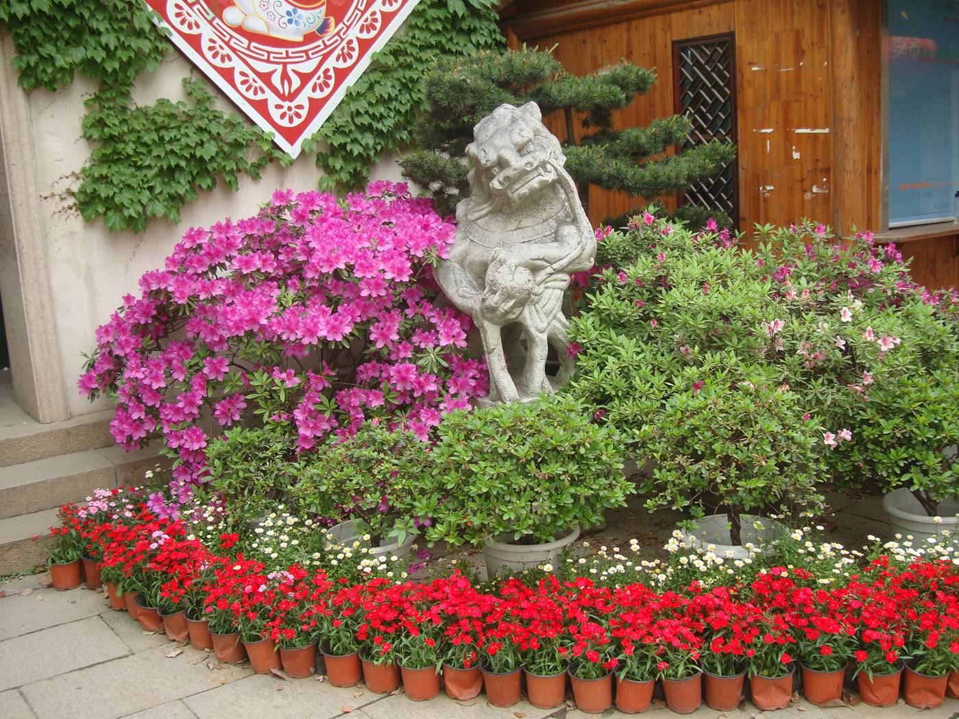 Picture:  The small flower bed beside the gate to Xi Hui Park, Wuxi, China.  With a Chinese gargoyle.