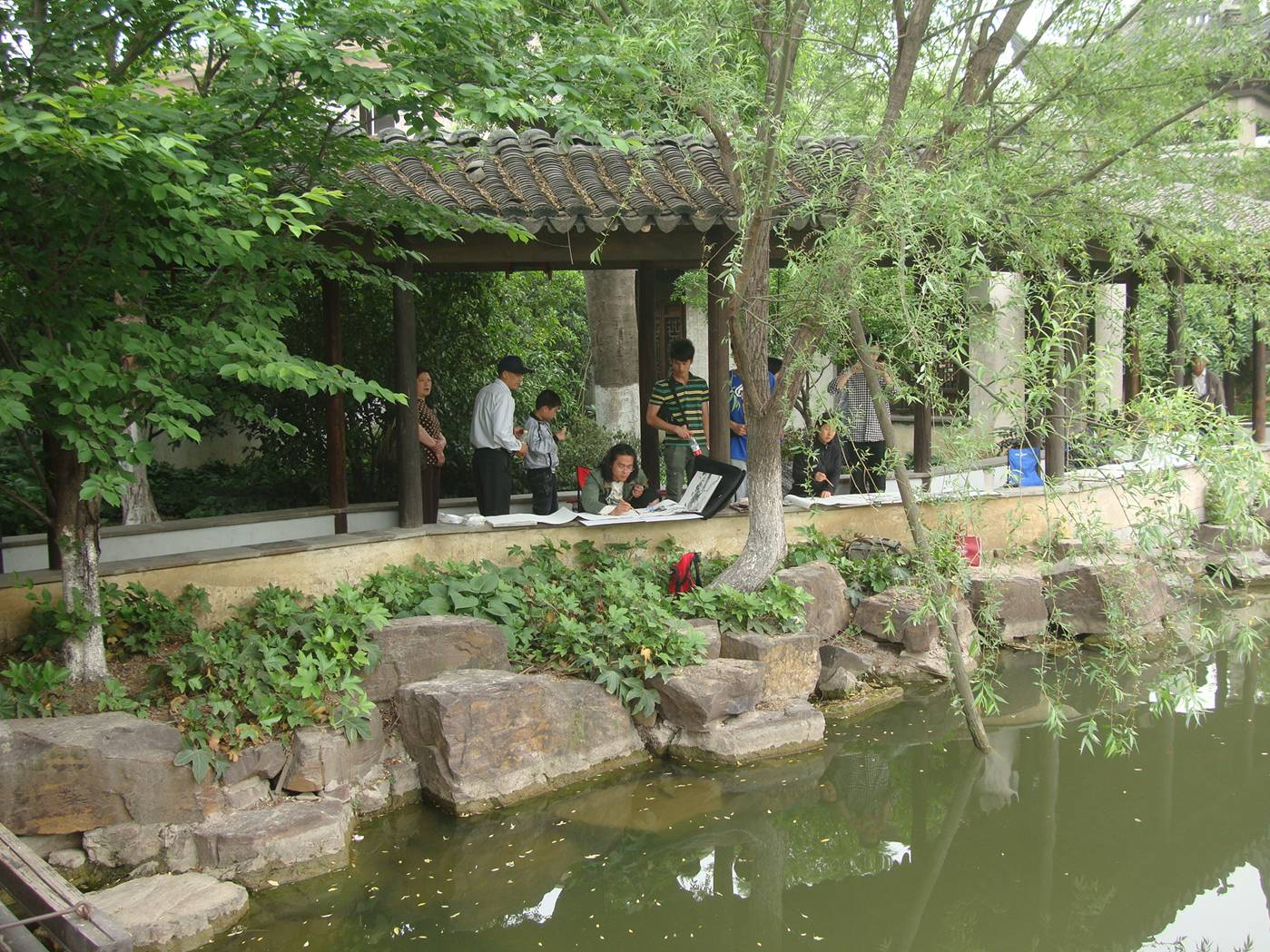Picture:  Painters at work at the pond on the grounds of the museum outside Xi Hui Park, Wuxi, China