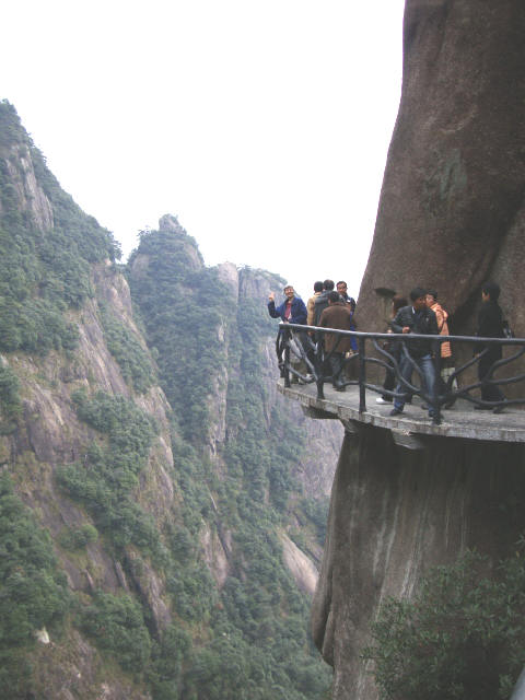 That's Ruth waving heroically from the corner on the impossible sidewalk,  San Qing Shan,  Jiangxi Province,  China