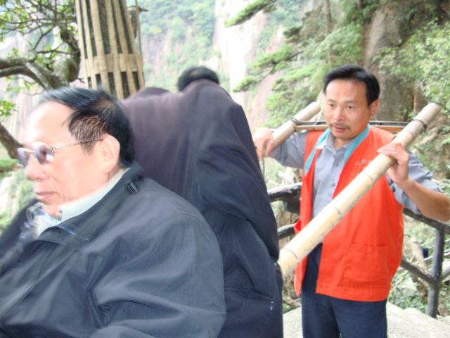 Low man or high man,  does it make a difference?  A sedan chair bearer on  San Qing Shan,  Jiangxi Province,  China