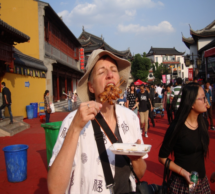 Picture: Ruth eats squid on a stick at the temple market.