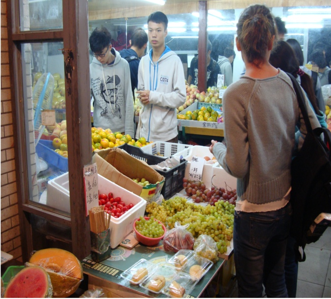 Picture:  Jiangnan University students in the campus fruit store late in the evening.