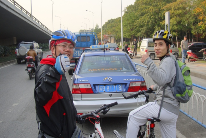 Picture:  A group of bike riders wearing helmets stopped briefly to check out the scene.  Wuxi, China