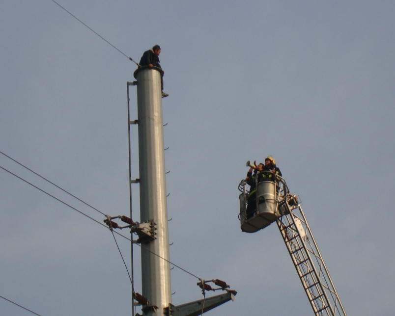 Picture:  Police try to talk the man down from his high perch on a power pole.  Wuxi, China