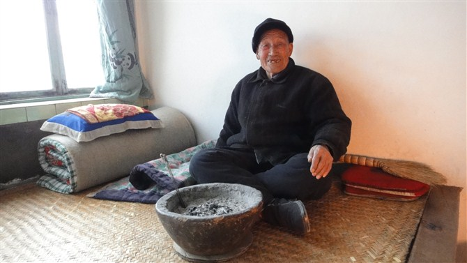 Picture: Meng Xiangj's grandfather age 90 smiling warmed by a charcoal brazier made of clay.