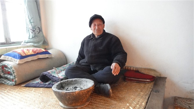 Picture: Meng Xiangj's grandfather age 90 warmed by a charcoal brazier made of clay.