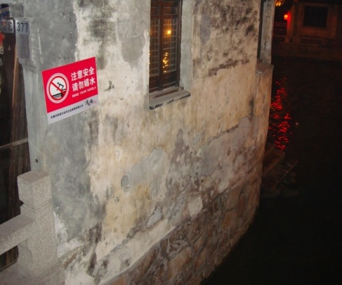 """Picture: a wall beside steps leading down to the canal.  A sign warns to """"Mind Your Safely""""  Wuxi, China."""