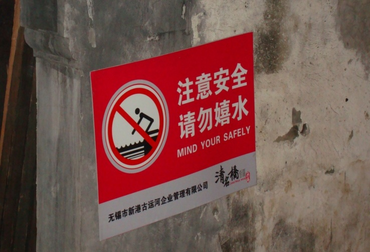 """Picture: Chinglish sign on a wall beside the canal. """"Mind Your Safely""""  Wuxi, China"""